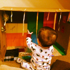 Sensory play box, complete with colours, shapes, fabrics, ribbons and a peek – a – boo window.