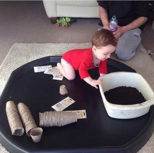 Oliver planting seeds.