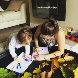 Oliver and Mummy doing crayon leaf rubbings.